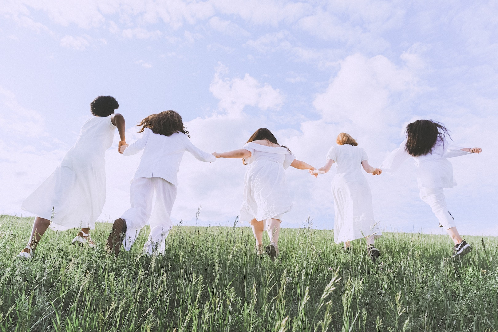 Image of a group of teenagers wearing white running through a field. TEDxMileHigh.